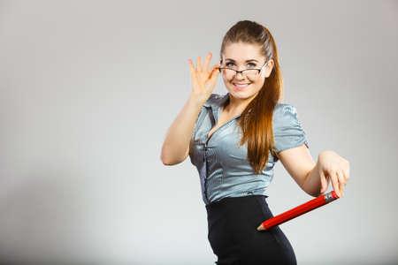 Teacher looking elegant woman wearing dark tight skirt, shirt and eyeglasses holding big oversized pencil 免版税图像