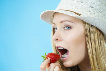 Young woman eating fresh strawberries fruits. Healthy meal.