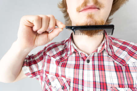 Bearded man having trouble with combing his beard using comb brush. Facial hair concept.