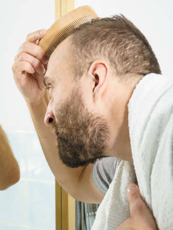 Adult man standing in front of the bathroom mirror brushing his short hair using comb. Guy investigating his receding hairline