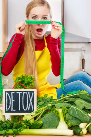 Young woman in kitchen having many green vegetables presenting board with detox sign.