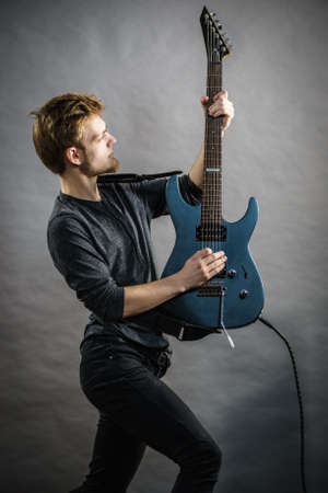 Man being passionate about his music hobby, playing electric guitar emotionally. Reklamní fotografie
