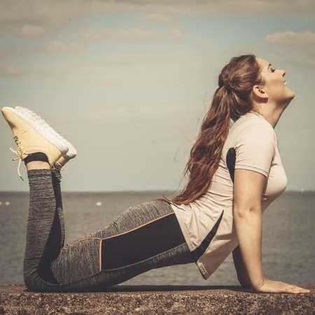 Super fit attractive young woman wearing fashionable outfit working out being active outside during sunny weather. Stretching her back or practice yoga next to sea Reklamní fotografie - 114910979