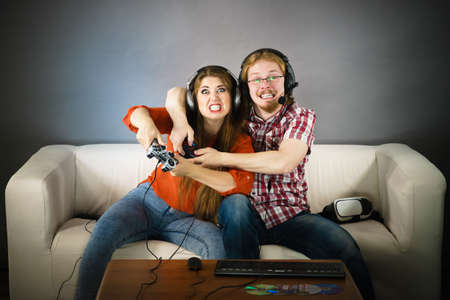 Couple enjoying leisure time by playing video games together, man and woman being emotional by game. Standard-Bild