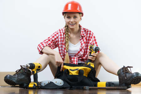 Woman with bag full of tools for her work at home. Girl working at flat remodeling. Building, repair and renovation.
