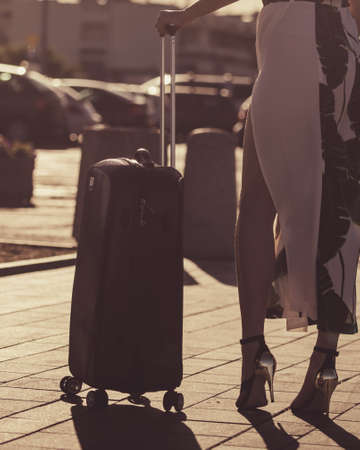 Fashionable woman arriving to new city wearing long dress and high heels, holding her suitcase on wheels admiring town after arrival. 写真素材
