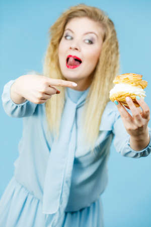 Sweet food and happiness concept. Funny excited blonde woman holding yummy choux puff cake with whipped cream, pointing with finger on it. On blue Zdjęcie Seryjne