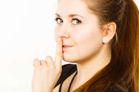 Woman showing silence shh gesture with finger close to mouth asking for being quiet