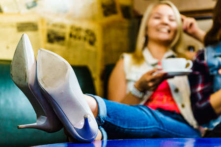 Woman relaxing drinking cup of tea or coffee in background. White high heels shoes in foreground close up. Free relax time concept.