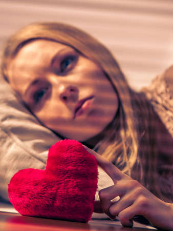 Sad lonely woman lying on bed being alone with heart shape.