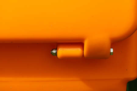 Close up of orange plastic box part detail with fastener screw bolts.