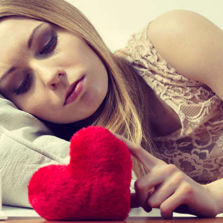 Sad lonely woman being alone holding red heart shape. Female missing someone during valentines.