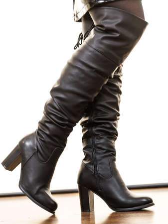 Close up on shiny black leather high heeled shoes. Long boots perfect for autumn. Fashion details concept. Stock Photo