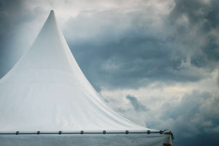Spiked roof of white party event tent against sky with dark clouds. Stok Fotoğraf