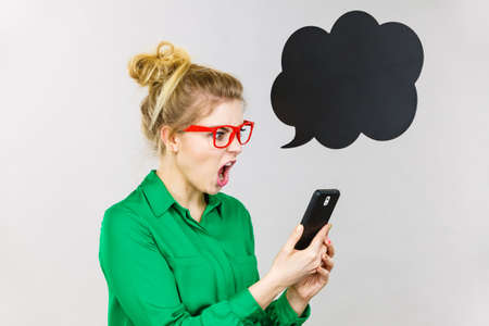 Angry business woman wearing green shirt and red eyeglasses looking at phone with black thinking or speech bubble next to her.