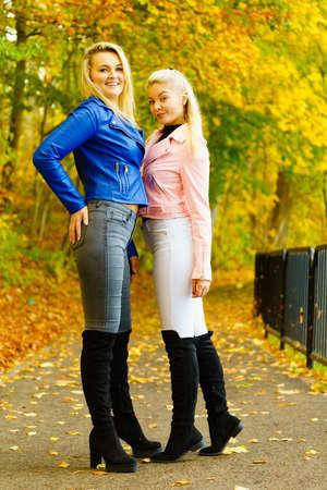 Dos amigas vistiendo traje de moda. Mujer con chaqueta de cuero azul marino bue rosa, jeans y botines negros altos. Foto de archivo