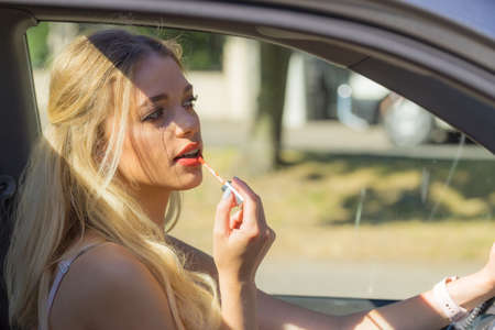Young attractive woman looking in rear view mirror painting her lips applying lipstick lip gloss make up while driving the car. Imagens
