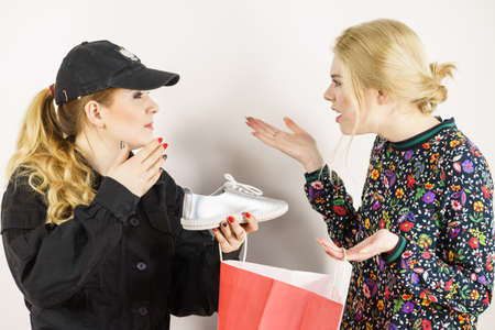 Young fashionable woman being caught on stealing shoes by female police officer. Customer being thief. Фото со стока