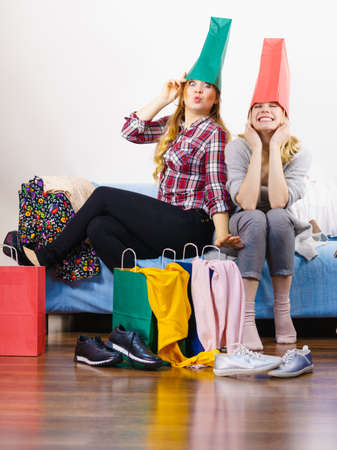 Two happy joyful women having fun after shopping, picking outfit in closet. Female friends fooling around playing with bags. Stock Photo