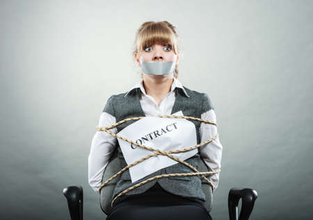 Afraid businesswoman bound by contract terms and conditions with mouth taped shut. Scared woman tied to chair become slave. Business and law concept. Banco de Imagens