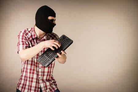 Crazy hacker man. Unrecognizable guy wearing black balaclava holding computer keyboard. Hate speech on the internet. Reklamní fotografie