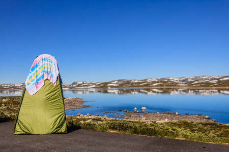 Portable shower bath tent on norwegian nature. National tourist Hardangervidda route. Camping tourism and bathing outdoor.