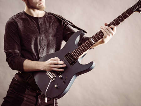 Young bearded man with electric guitar. Adult person is holding instrument and playing. Hobby, music concept, on grey