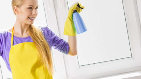 Young housewife cleaner woman washing window at home using spray detergent. Cleaning concept Фото со стока - 116586485