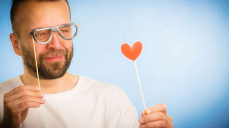 Funny adult guy flirting hoping for romance. Man holding heart shape and eyeglasses on stick, making fun.