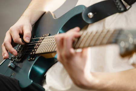 Close up of man playing on electric guitar during gig or at music studio. Musical instruments, passion and hobby concept.