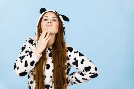 Happy teenage girl in funny nightclothes, pajamas cartoon style making silly face, positive face expression, studio shot on blue.