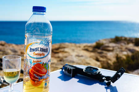 TORREVIEJA, SPAIN - JANUAR 30, 2019: Polish Zywiec Zdroj flavored apple drink in bottle on table at Torrevieja coast on Januar 30, 2019, Spain. Zywiec Zdrój is leader in category of waters in Poland.