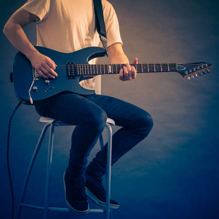 Man playing on electric guitar during gig. Musical instrument. Teenage boy having music hobby.