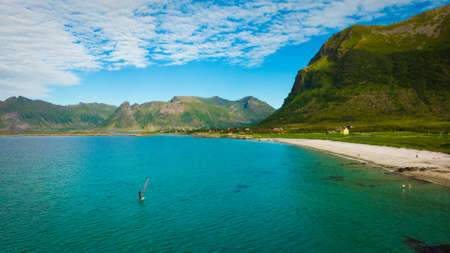 Aerial view of surfer in clear water beach, high mountains in the background. Lofoten Norway 스톡 콘텐츠