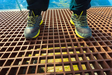 Tourist feet on Dalsnibba viewpoint, Geiranger Skywalk platform metal floor surface and view on mountains landscape, Norway.