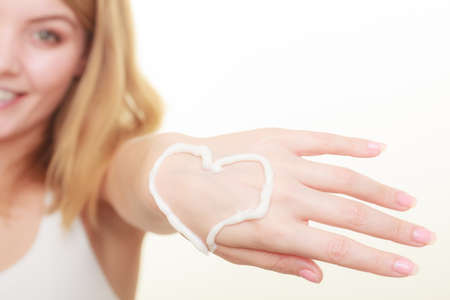 Beauty, cosmetics, concept. Smiling woman having cream on her hand, heart shape. Studio shot on white background