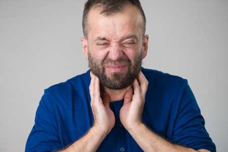 Erwachsener Mann, der harte Hals-, Nacken-, Lymphknotenschmerzen fühlt. Konzept für Gesundheitsprobleme und -probleme. Standard-Bild