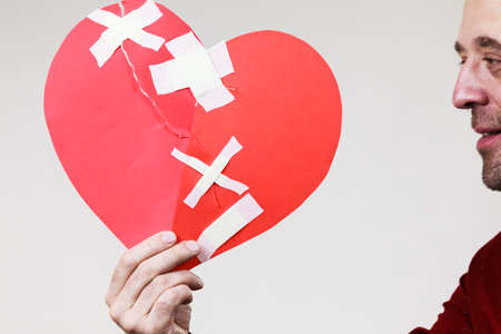 Healed love. Valentines Day concept. Adult smiling man holding big red heart fixed with plaster bandage. Male healing relationship. Stock fotó - 117212473