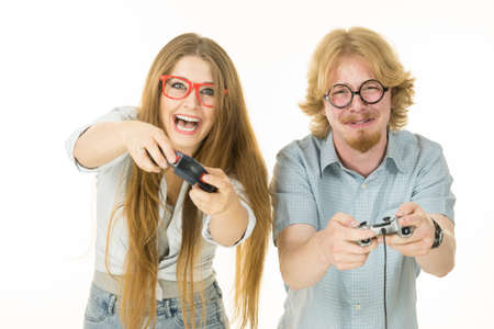 Very emotional couple enjoying leisure time by playing video games together. Studio shot isolated Standard-Bild