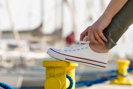 Person adjusting, tying up laces in white sneakers, casual shoes on yellow bollard pin. Outdoor footwear perfect for warm weather.