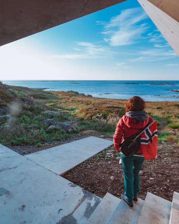 Tourist woman with norwegian flag enjoying sea coast view from Bukkekjerka rest stop area on Andoya island, Vesteralen archipelago, Norway. Stock Photo