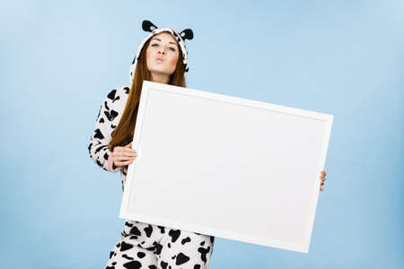 Positive teenage girl in funny nightclothes, pajamas cartoon style with blank empty banner board. Advertisement copyspace.