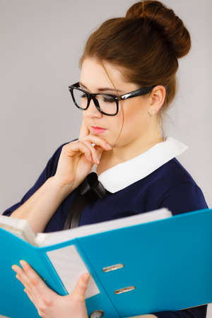 Woman office worker agent holding blue file folder in hands. Young elegant businesswoman or secretary with documents bills. Thinking face expression. Business and paperwork on grey 版權商用圖片