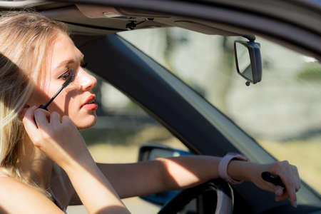 Young attractive woman looking in rear view mirror painting her eyelashes applying mascara make up while driving the car.