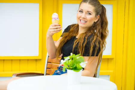 Happy funny young woman with long brown hair eating ice cream having fun.