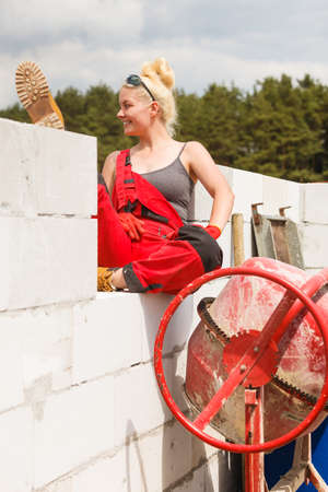 Strong woman worker working with red concrete cement mixer machine on house construction site. Industrial work equipment concept. Banque d'images - 117939231
