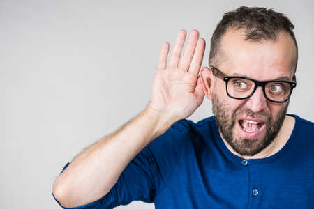 Man in eyeglasses having troubles with hearing, being deaf. Guy gesturing eavesdropping with hand close to ear, listening gossips.
