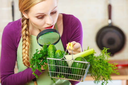 Buying healthy dieting food concept. Woman in kitchen having many green vegetables looking through magnifier at shopping basket trolley. Imagens
