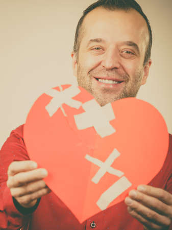 Healed love. Valentines Day concept. Adult smiling man holding big red heart with plaster. Male healing relationship. Banco de Imagens - 118162100
