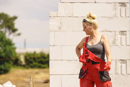 Happy blonde woman wearing dungarees about to do some work on construction site. Women power, gender equality, industrial worker.
